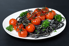 Black spaghetti with baked tomatoes, parmesan Royalty Free Stock Photography