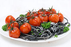 Black spaghetti with baked tomatoes and parsley, close-up Royalty Free Stock Photography