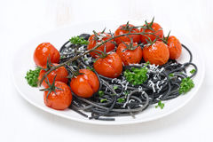 Black spaghetti with baked tomatoes and parsley Stock Image