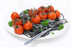 Black spaghetti with baked tomatoes and parsley on white plate Stock Photography