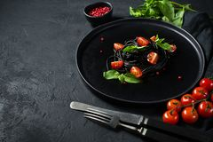 Black spaghetti with Basil and cherry tomatoes, vegetarian pasta. Black background, top view, space for text. stock photo