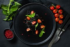 Black spaghetti with Basil and cherry tomatoes, vegetarian pasta. Black background, top view, space for text. stock photography
