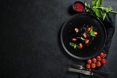 Black spaghetti with Basil and cherry tomatoes, vegetarian pasta. Black background, top view, space for text. royalty free stock image