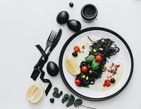 Black spaghetti with basilica and tomatoes on table. Black Easter eggs stock photography