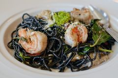 Black Spaghetti with mixed seafood and garlic in white plate stock images