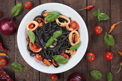 Black spaghetti pasta with mussels and squid rings Stock Photos