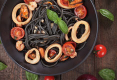 Black spaghetti pasta qith mussels and squid rings. Italian black spaghetti pasta with mussels and squid rigns Stock Photo