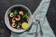 Black spaghetti pasta with shrimps, basil and lime served on a gray plate. Top view, black stone background. royalty free stock photos