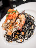 Black spaghetti with prawn. In white plate isolated Royalty Free Stock Photography
