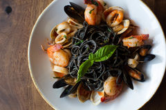 Black Spaghetti with seafood. Black spaghetti pasta with mussels, calamari, and shrimp topped with basil Stock Images