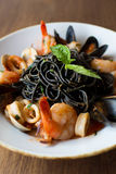 Black Spaghetti with seafood. Black spaghetti pasta with mussels, calamari, and shrimp topped with basil Stock Photography
