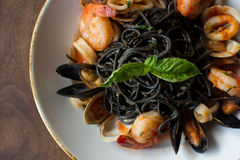 Black Spaghetti with seafood. Black spaghetti pasta with mussels, calamari, and shrimp topped with basil Royalty Free Stock Image