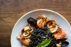 Black Spaghetti with seafood. Black spaghetti pasta with mussels, calamari, and shrimp topped with basil Royalty Free Stock Photography