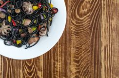 Black spaghetti with seafood and vegetables on a brown wooden background copy space top view stock photo