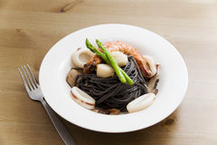 Black spaghetti with seafood on wooden table Royalty Free Stock Image