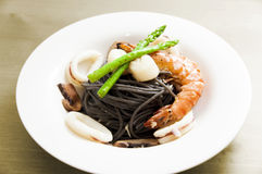 Black spaghetti with seafood on wooden table Royalty Free Stock Images