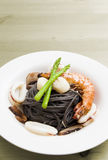 Black spaghetti with seafood on wooden table Stock Photo