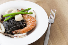 Black spaghetti with seafood on wooden table Stock Image