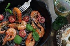 Black spaghetti with shrimp , tomatoes, Basil and white wine. White wine and black spaghetti with shrimp, Basil and cherry tomatoes Stock Photos