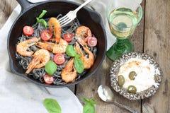 Black spaghetti with shrimp , tomatoes, Basil and white wine. White wine and black spaghetti with shrimp, Basil and cherry tomatoes Stock Image