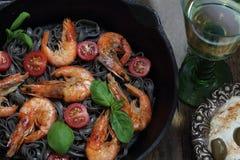 Black spaghetti with shrimp , tomatoes, Basil and white wine. White wine and black spaghetti with shrimp, Basil and cherry tomatoes Stock Photography