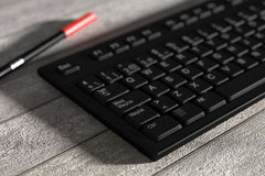 Black spanish keyboard and red marker on wooden table. 3d rendering of a black spanish keyboard and red marker on wooden table. From above Stock Photo