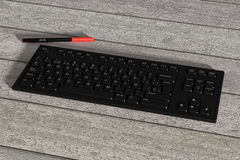 Black spanish keyboard and red marker on wooden table. 3d rendering of a black spanish keyboard and red marker on wooden table. From above Royalty Free Stock Image