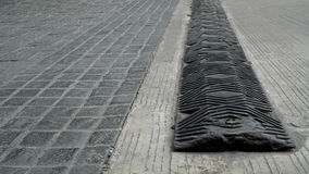 Black speed bump for slowing traffic, reduce speed down on the t. Black speed hump for slowing traffic, reduce speed down on the tile and cement road royalty free stock images