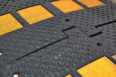 Black speed bump with yellow reflectors Stock Image