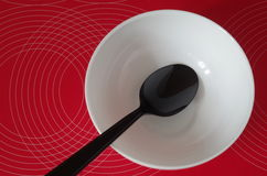 Black spoon in a white bowl on a red tablecloth Stock Image