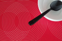 Black spoon in a white bowl on a red tablecloth Stock Photo