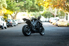 Black Sport Bike Parked in Center of Residential Street at Daytime Royalty Free Stock Images