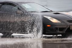 Black sport car on ice. With water spray from wheels Royalty Free Stock Image