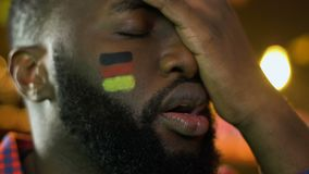 Black sport fan with German flag on cheek upset about favorite team losing game