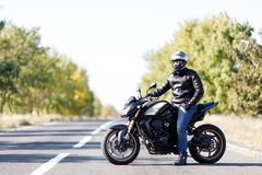 A close-up of a motorcycle stands on the road with its owner alone. Black, a sport motorcycle close-up costs only on the road with its owner Royalty Free Stock Photo
