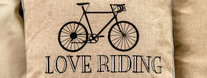 Black sport retro bike embroidered on gold cushion with love rid royalty free stock image