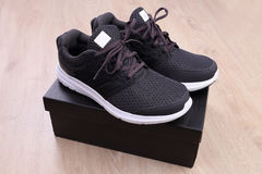 Black sport shoes with box on wooden background Royalty Free Stock Photography