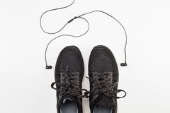 Black sport shoes with headphone on white background Stock Photos