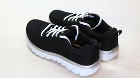 Black sport unisex sneakers with white sole and white laces on white background stock image