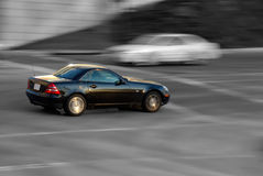 Black Sports Car. A black sports car speeds down the road with a black and white background Stock Photography