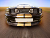 Black sports car on the country road Royalty Free Stock Photos