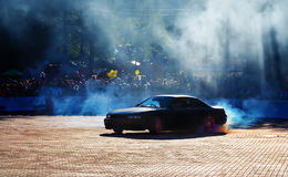 Black sports car smokes wheels Royalty Free Stock Image