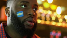 Black sports fan with Argentinian flag on cheek upset about favorite team loss