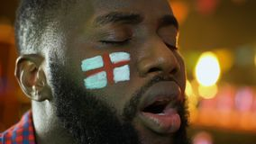 Black sports fan with English flag on cheek upset about favorite team loss