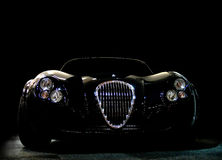 Black Sportscar. A black roadster sportscar on a black background Stock Photos