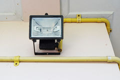 Black Spotlight bulb(Selective focus) is installed on cream colo. R wall with yellow polymer vinyl chloride pipe which contains electric cables in Stock Image