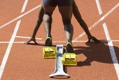 Black sprinter start. Dark-skinned sprinter in start position prepares for the start Royalty Free Stock Images