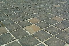 Black square paving stones with large distances between the stones. Building background. Royalty Free Stock Images