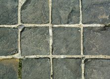 Black square paving stones with large distances between the stones. Building background. Stock Photography