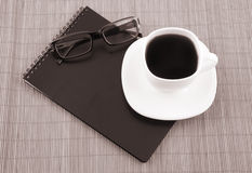 Black squared notebook with cup of coffee Stock Photography